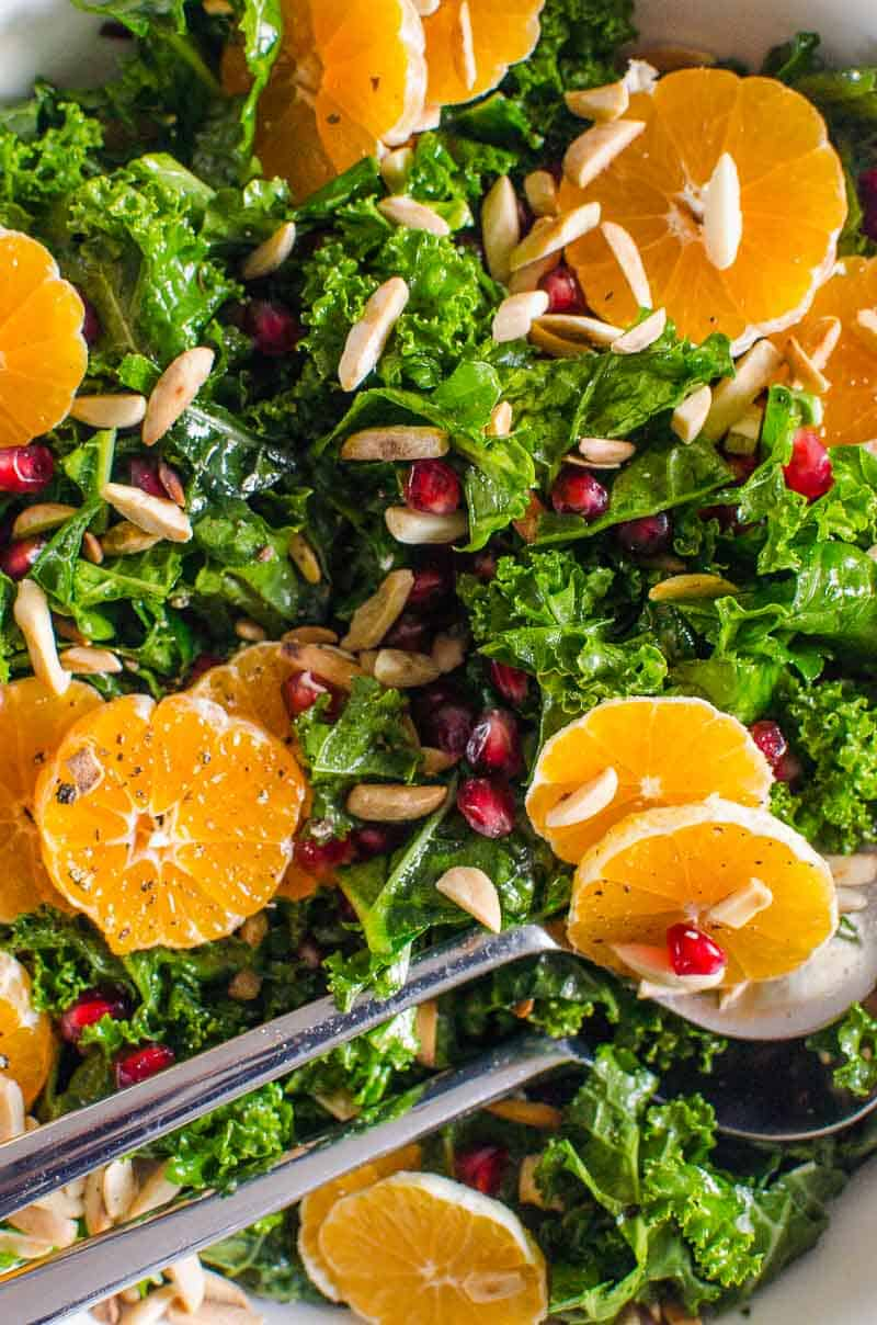 Massaged Kale Salad with Winter Fruit in bowl with metal serving spoons