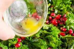 pouring kale salad dressing over kale salad with pomegranates