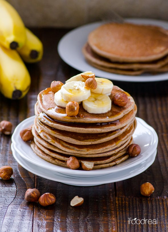 Cottage Cheese Protein Pancakes on plate topped with bananas and hazelnuts
