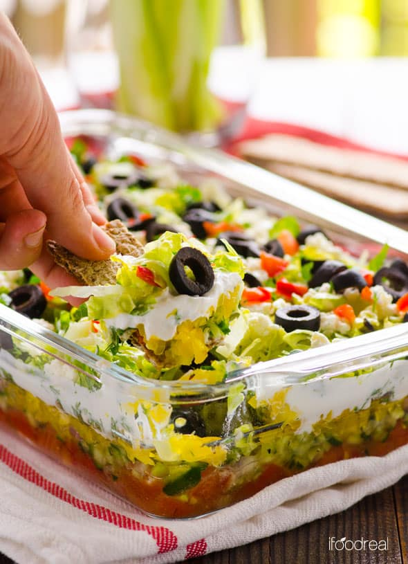 Greek Salad Layered Dip Recipe is a fresh healthy appetizer made with lettuce, tomatoes, feta cheese, olives and Greek yogurt. Serve with pita chips or celery sticks. | ifoodreal.com