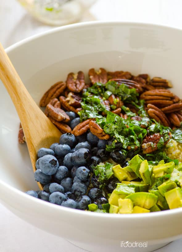 Mixing ingredients for Blueberry Quinoa Salad in a white bowl