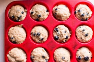 Healthy Blueberry Muffins batter in red muffin tin
