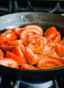 sliced tomatoes in cast iron skillet cooking on a stove