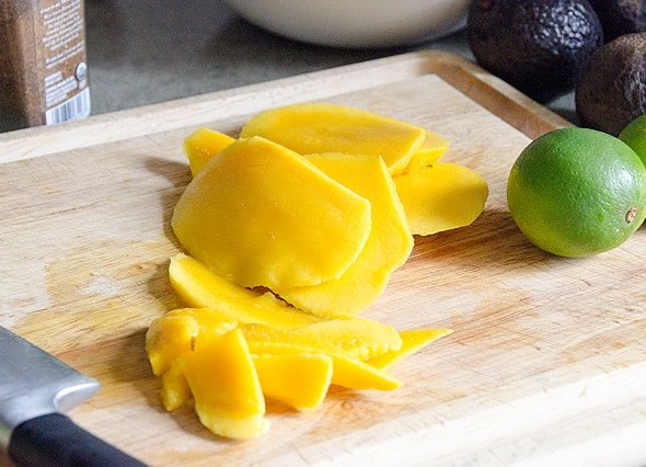 Sliced mango on cutting board with lime.