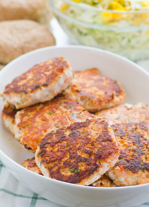 Delicious salmon burgers recipe with red lentils to make them more affordable and nutritious. Topped with delicious slaw. My kids licked the plates. | ifoodreal.com