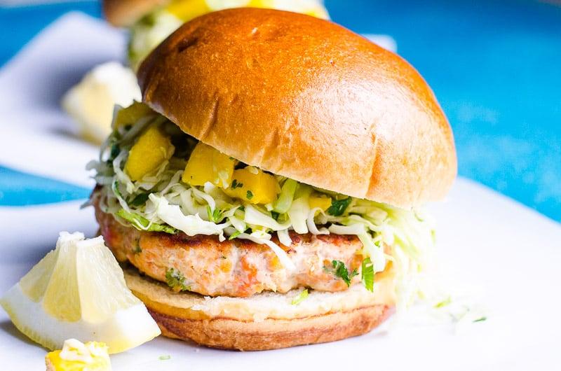 salmon burger on a bun topped with mango slaw