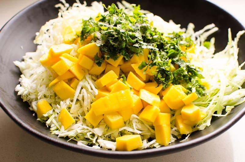 diced mango, shredded cabbage, cilantro in black bowl