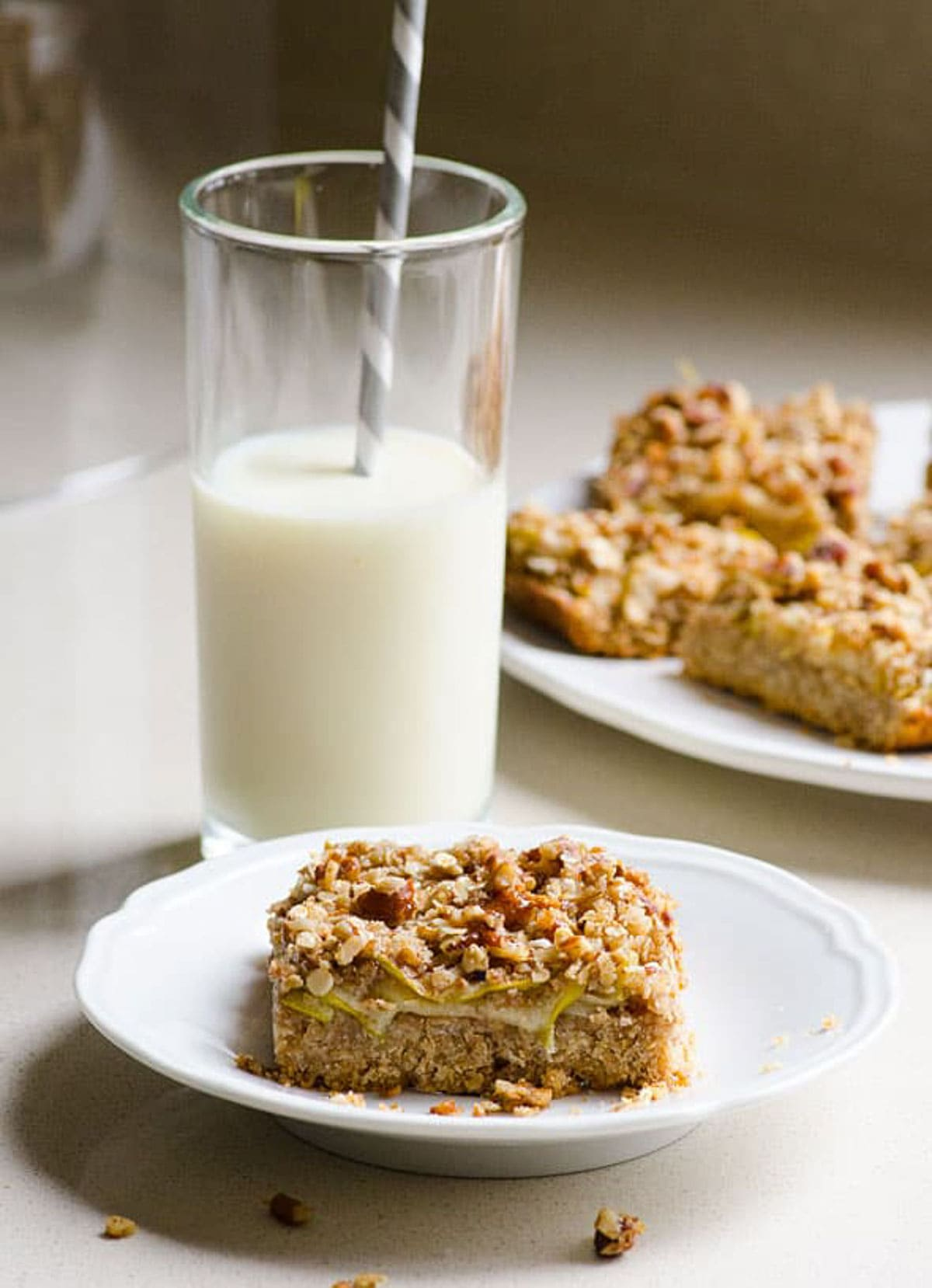 Apple Oatmeal Bars with Honey on plate beside a glass of milk