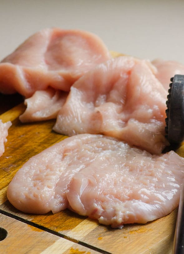 pounding chicken breast on cutting board