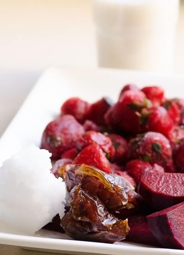 Plate of raw beets, strawberries, dates, apples and superfood coconut oil.