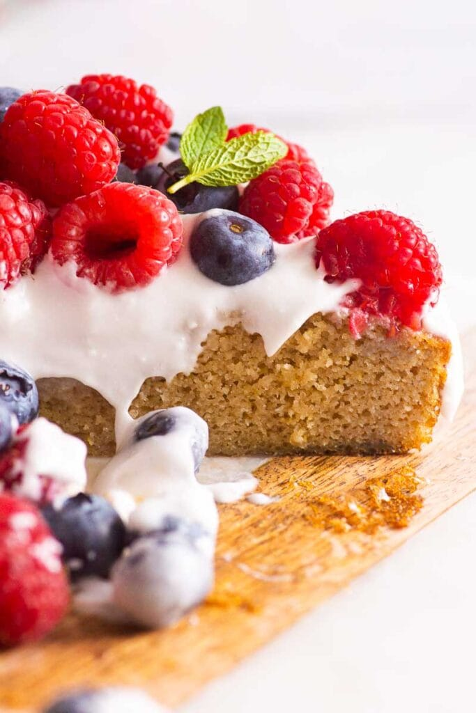 sliced almond flour cake topped with whipped cream and berries