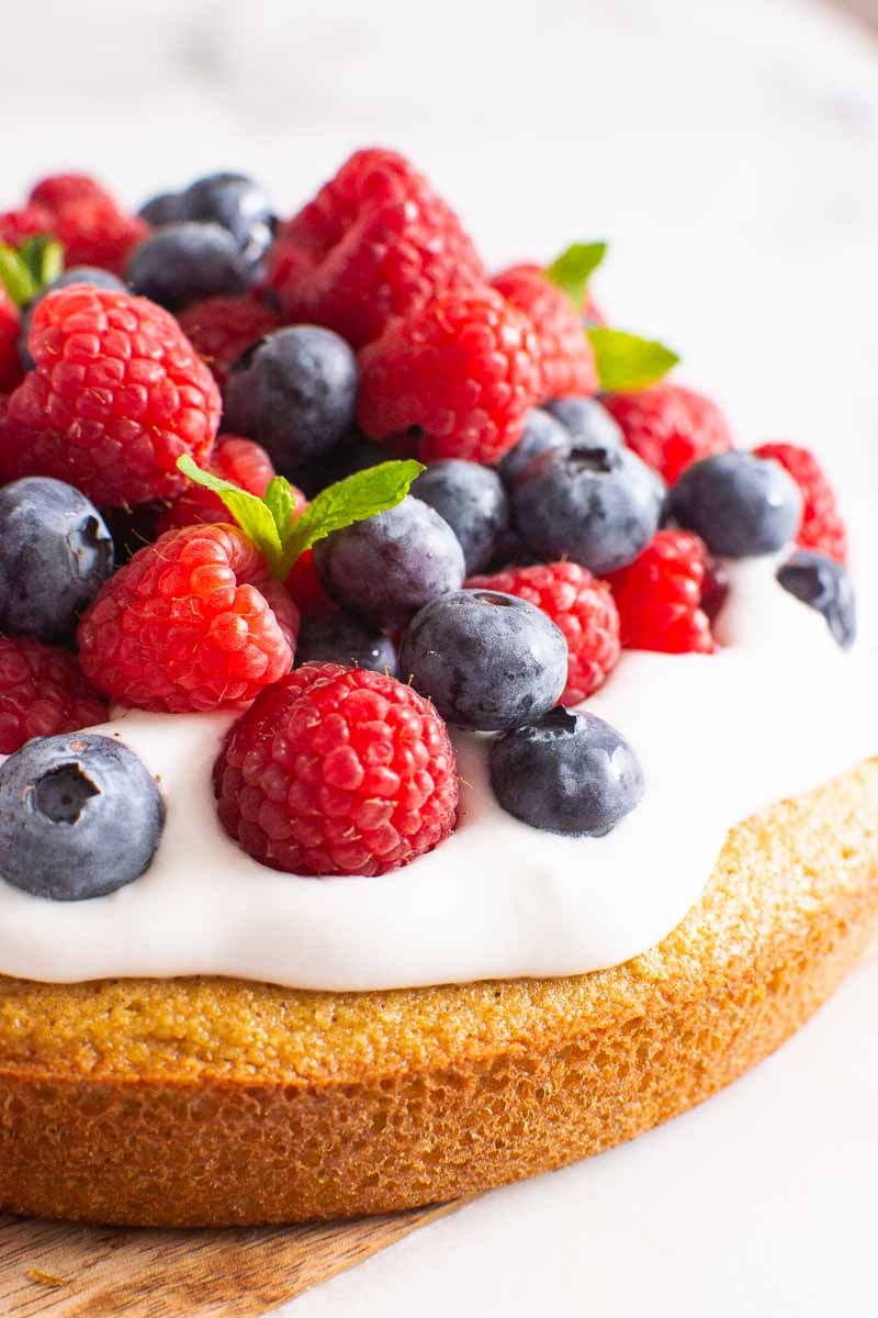 healthy almond flour cake topped with coconut whipped cream and berries