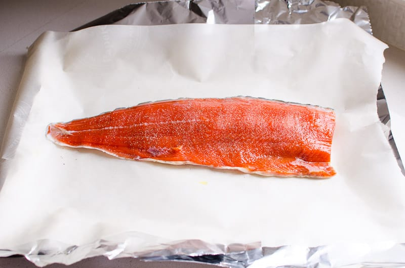 salmon fillet laying on top of parchment paper and foil