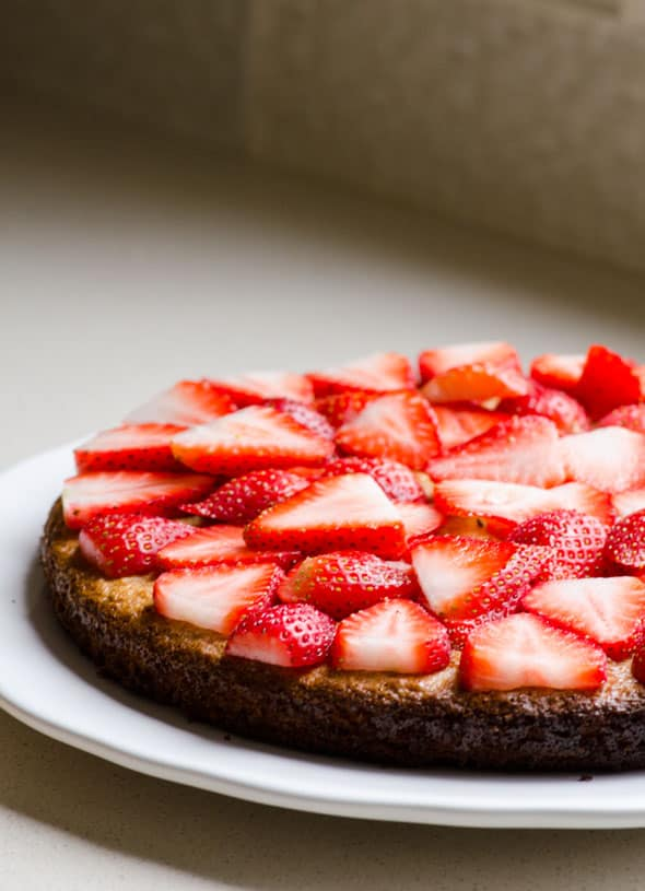 Half of Healthy Almond Cake topped with sliced strawberries