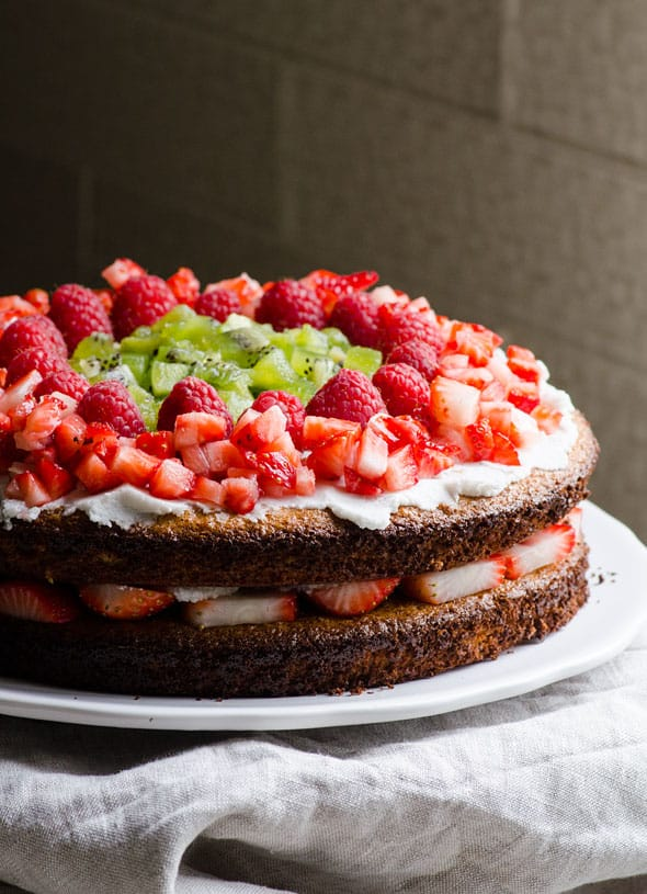 healthy almond cake with coconut cream, strawberries, raspberries and kiwi