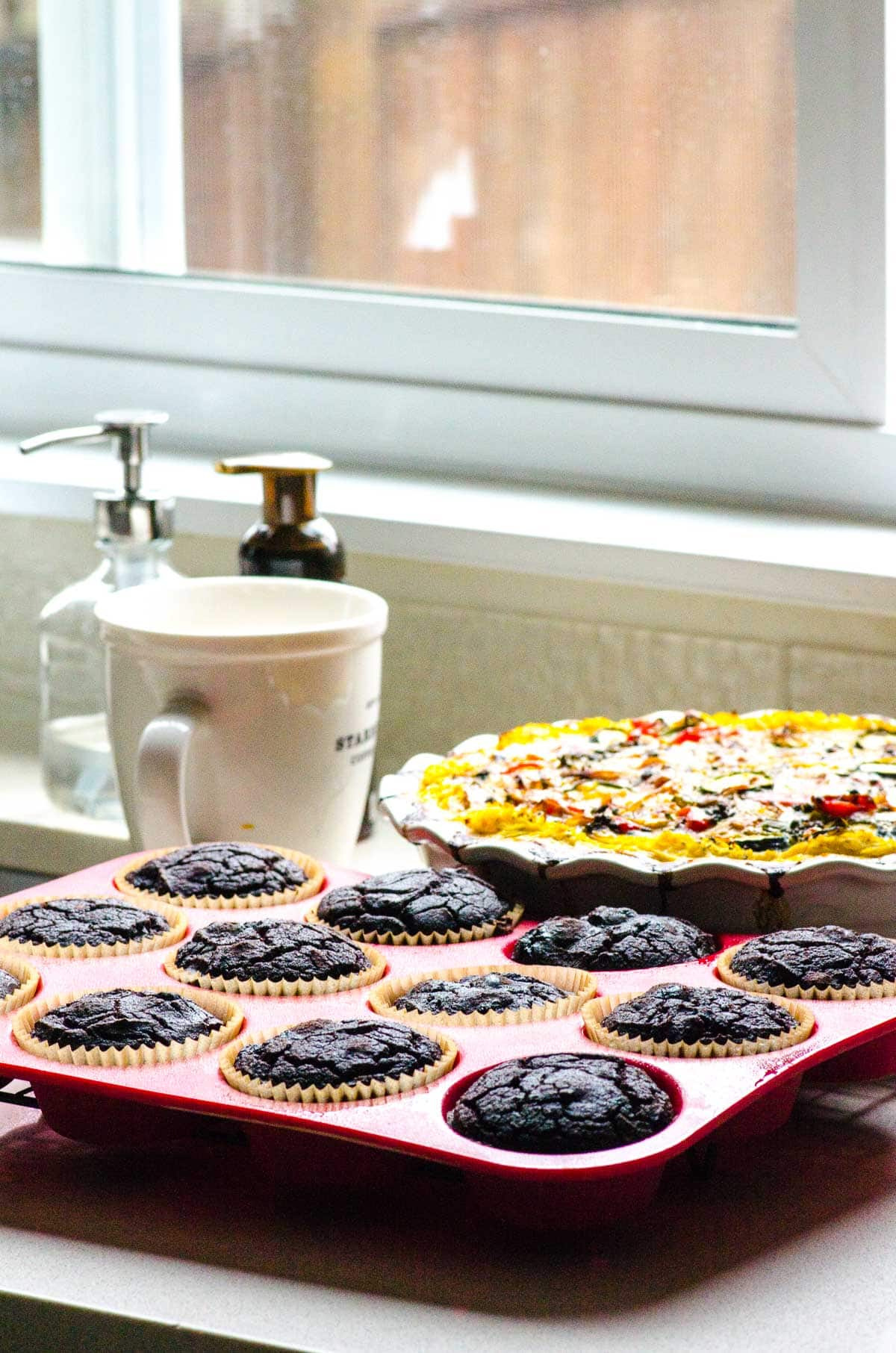 Cherry & Chocolate Coconut Flour Muffins  in muffin tins by the window