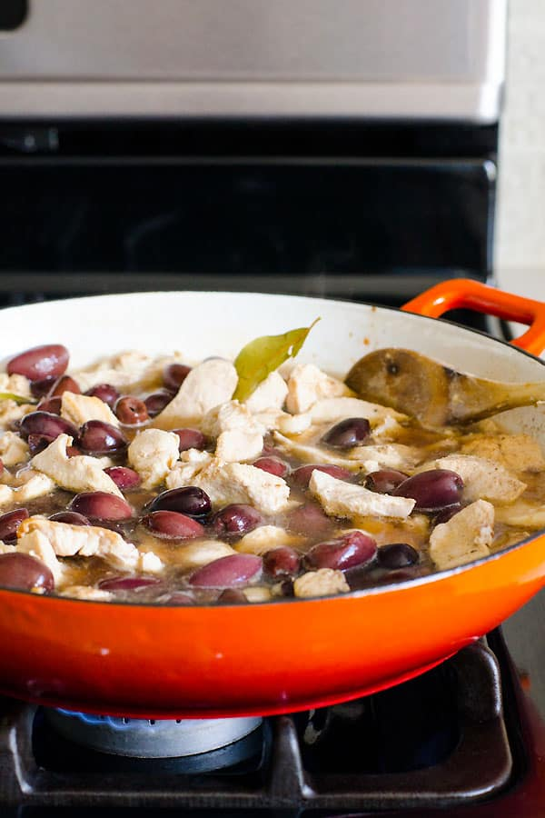 chicken simmering with and olives on the stove