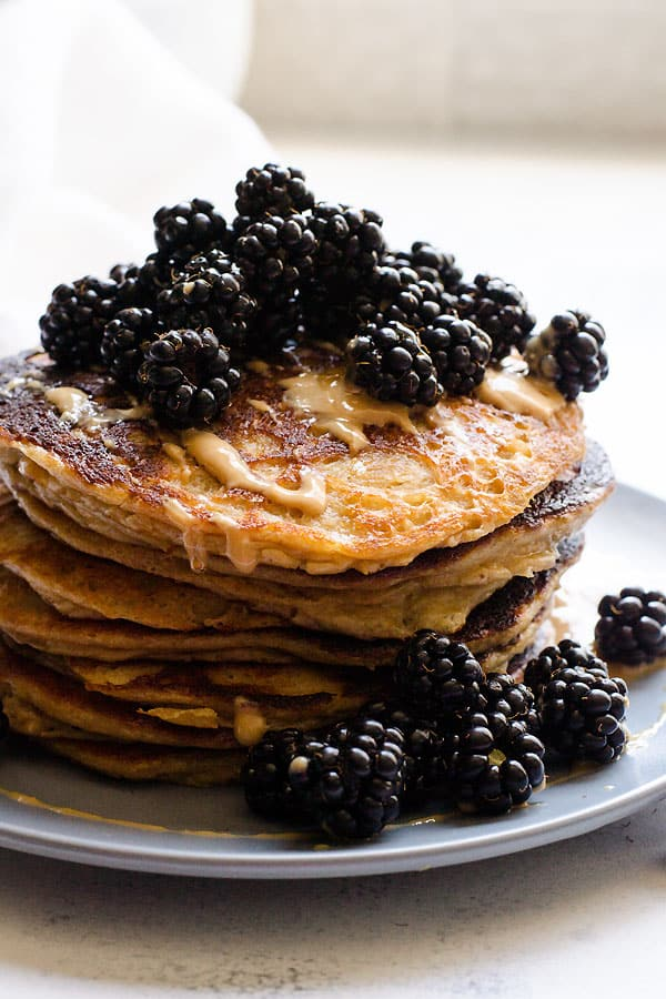 Stack of Peanut Butter Protein Pancakes on plate topped with blackberries