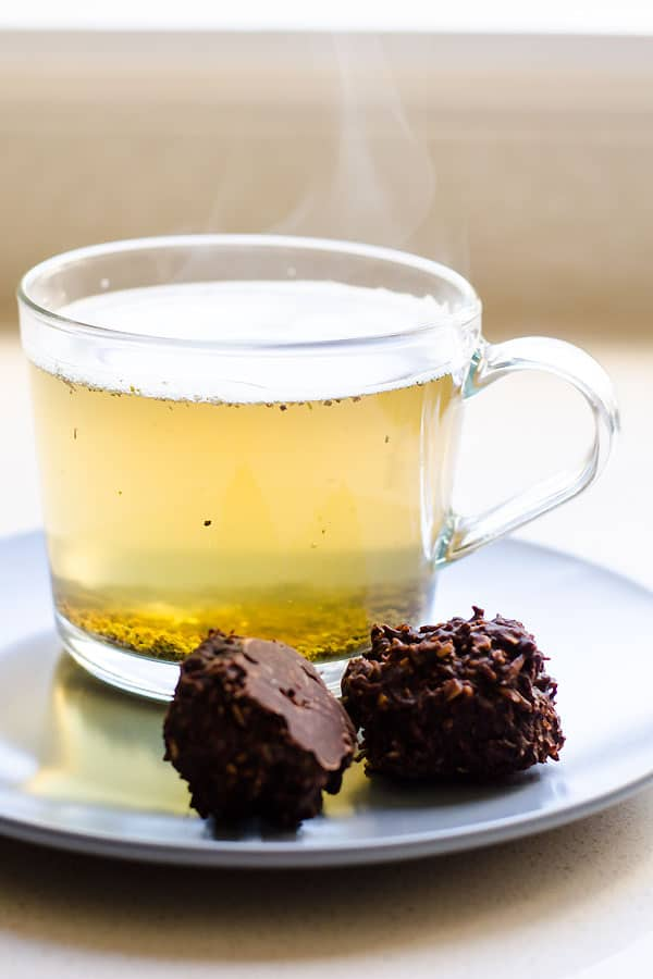 2 Chocolate Coconut Balls on a plate with a cup of tea