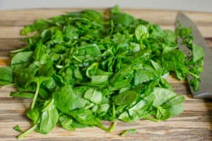 chopped spinach on wood cutting board