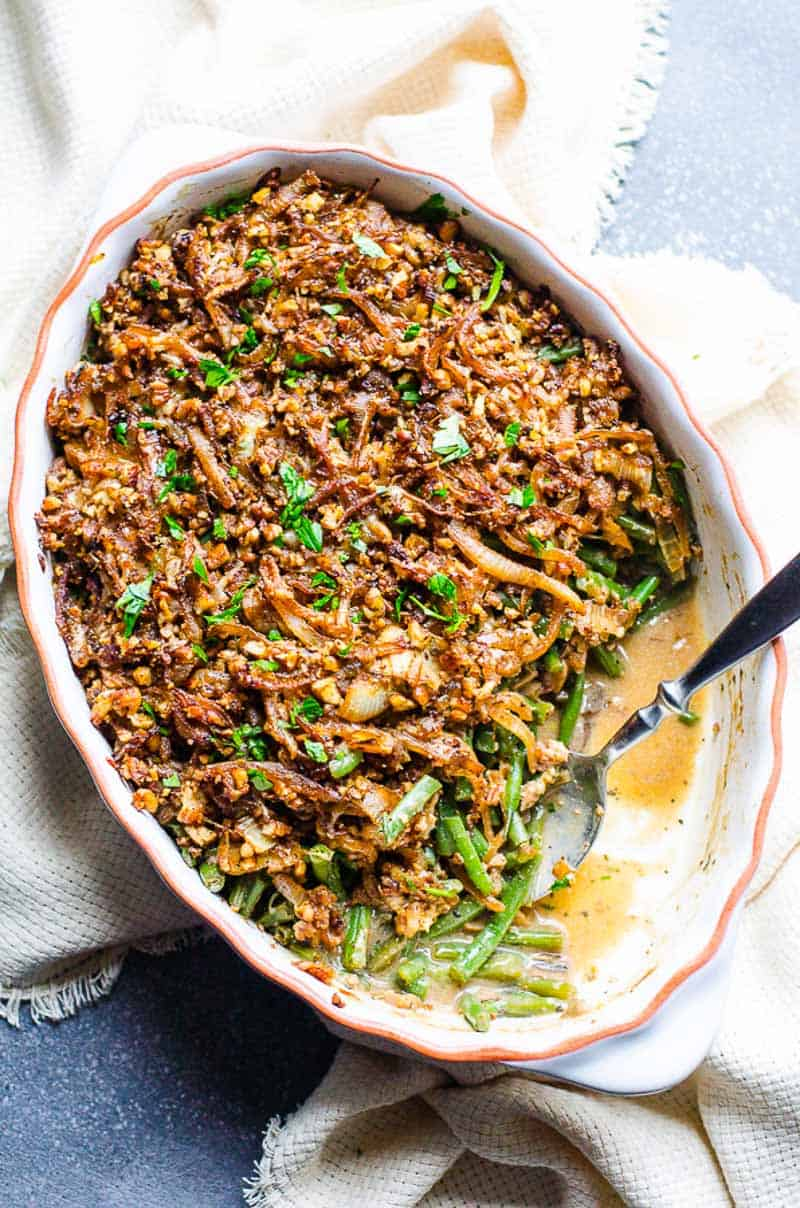 Healthy Green Bean Casserole in a white baking dish with a spoon