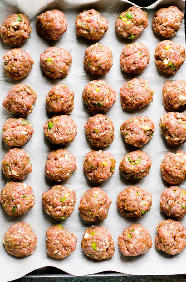 Mexican Meatballs lined up on parchment paper on baking tray; unbaked