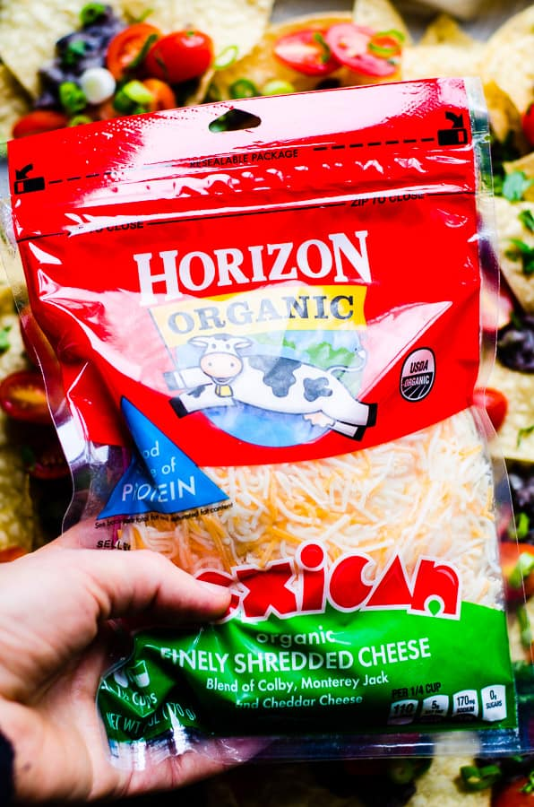 Spicy Black Bean Nachos Recipe - a thin layer of tortilla chips loaded with zesty lime black bean and jalapeño sauce, juicy tomatoes, green onions and cilantro, then covered with melted cheese. Flavour in every single bite!   ifoodreal.com
