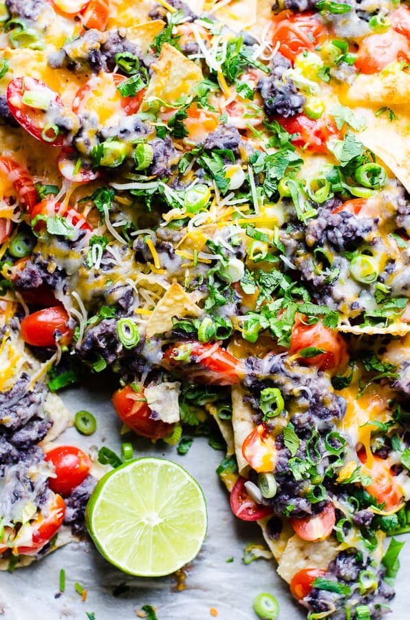 Spicy Black Bean Nachos Recipe - a thin layer of tortilla chips loaded with zesty lime black bean and jalapeño sauce, juicy tomatoes, green onions and cilantro, then covered with melted cheese. Flavour in every single bite! | ifoodreal.com
