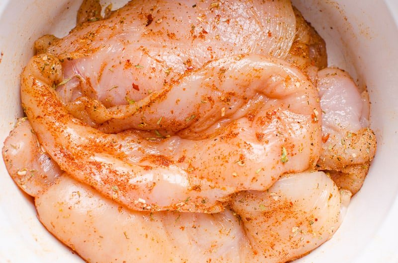 raw chicken covered in cajun seasoning in a bowl