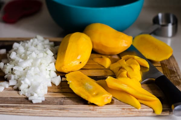 chopped onion and sliced mango on cutting board