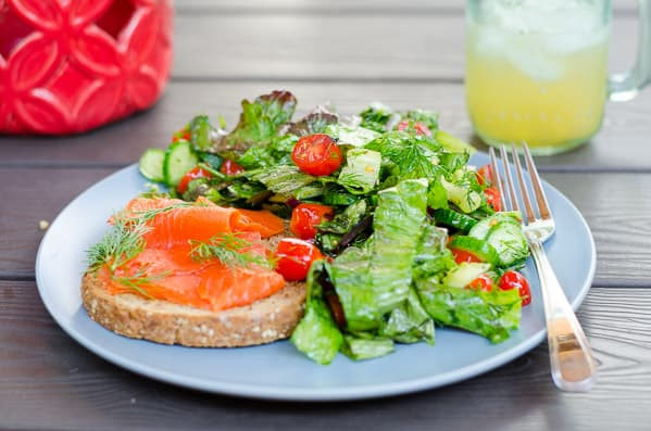 smoked salmon toasts and Lettuce Salad with Tomato and Cucumber served on blue plate