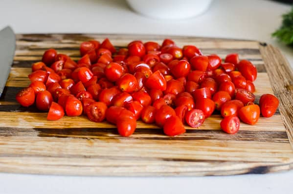 sliced grape tomatoes on wood cutting board