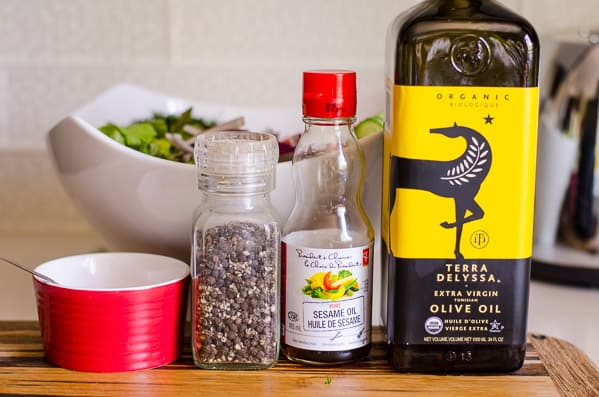 salt, black pepper, sesame oil and olive oil lined up on kitchen counter