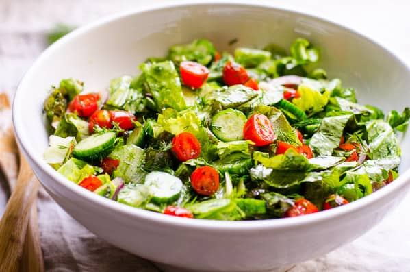 Lettuce Salad with cucumbers and tomatoes in white bowl