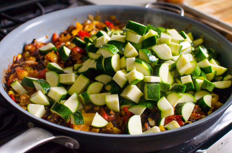 sauteing bell peppers, chicken and zucchini in a skillet