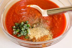 tomato sauce, spices and jalapeno in a bowl with a spoon