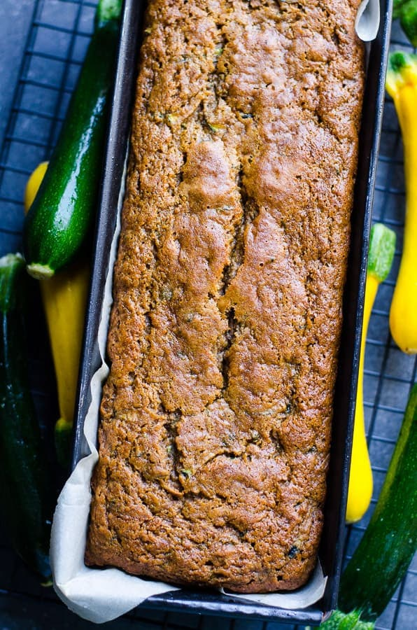 Healthy Zucchini Bread in a loaf pan with fresh zucchini by the sides