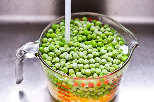 Frozen vegetables in a measuring cup under running water