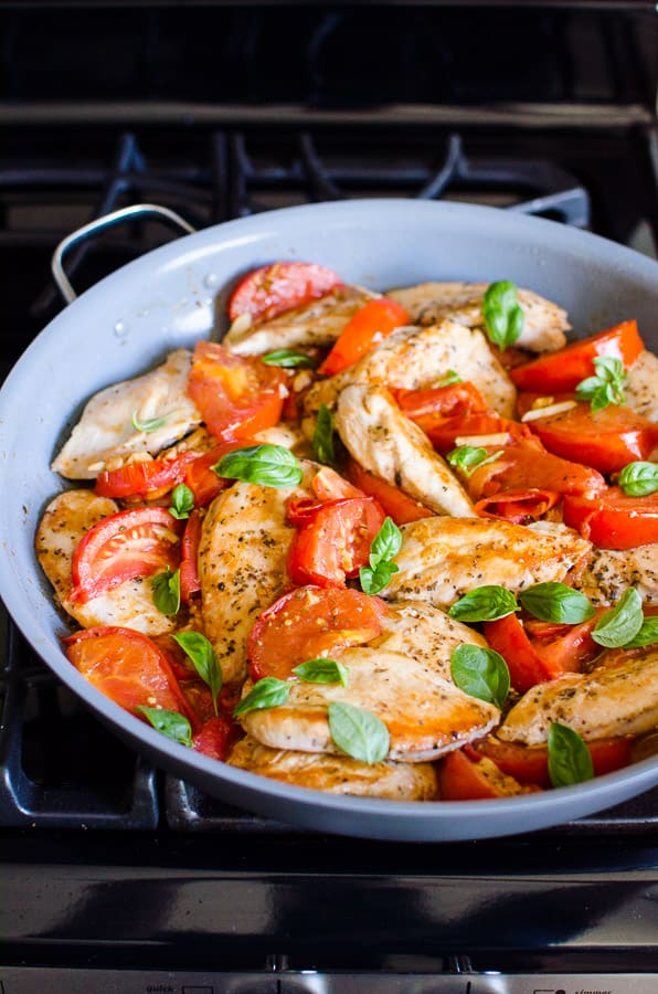 Chicken and tomatoes garnished with basil in a skillet