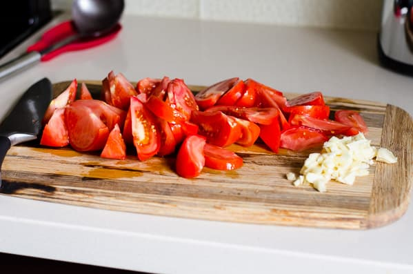 sliced tomatoes and minced garlic on cutting board