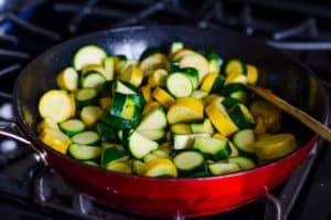 cooking sliced zucchini in a skillet