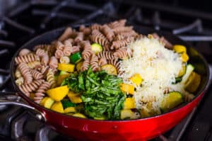 pasta, veggies, basil and cheese in a skillet on a stove