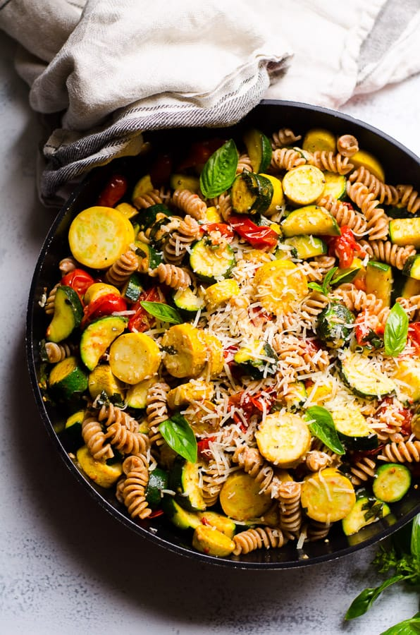 Pasta with Zucchini and Tomatoes in a skillet and linen towel nearby