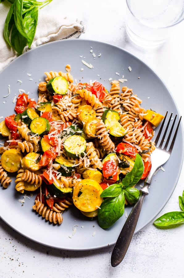 Pasta with Zucchini and Tomatoes garnished with parmesan cheese on a plate