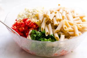 pasta, parsley, tomatoes, bell pepper, cheese in a bowl with a spoon