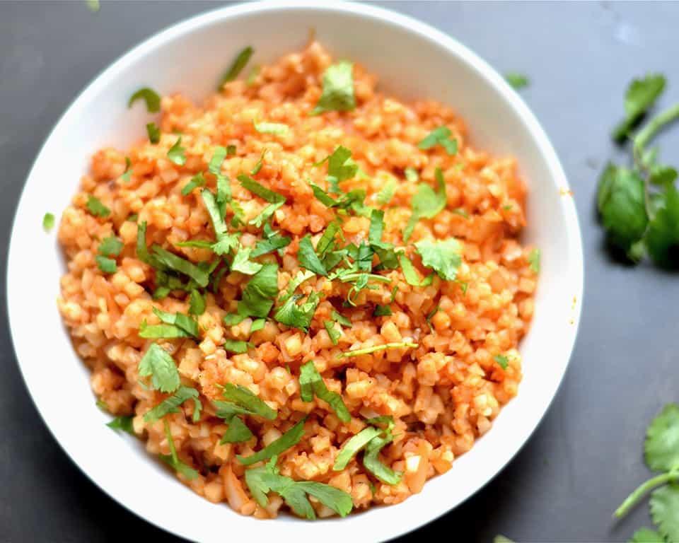 Cauliflower Spanish Rice in white bowl with garnish