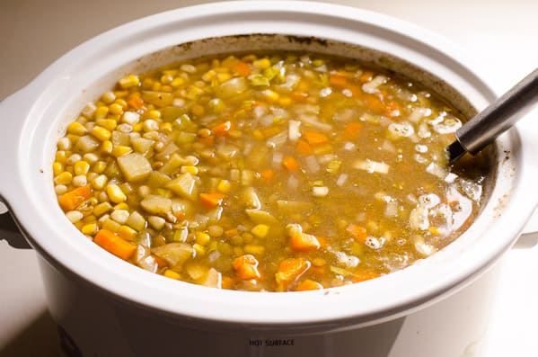 Slow Cooker lentil soup with ladle in crockpot