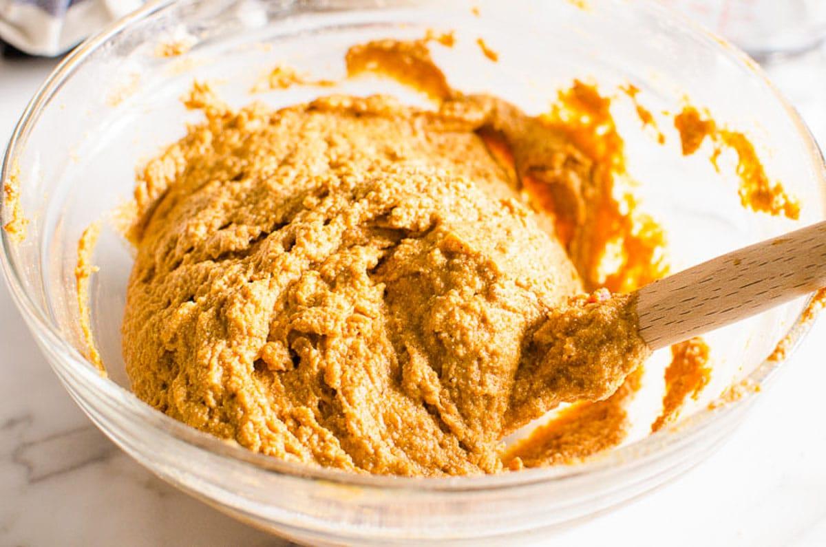 gently folding whole wheat flour into pumpkin muffins batter