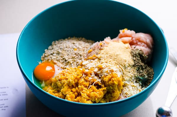 unmixed ingredients in blue bowl; eggs, lentils, spices, turkey, oats