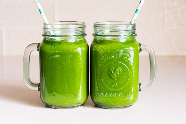 2 jars with green smoothie and straws